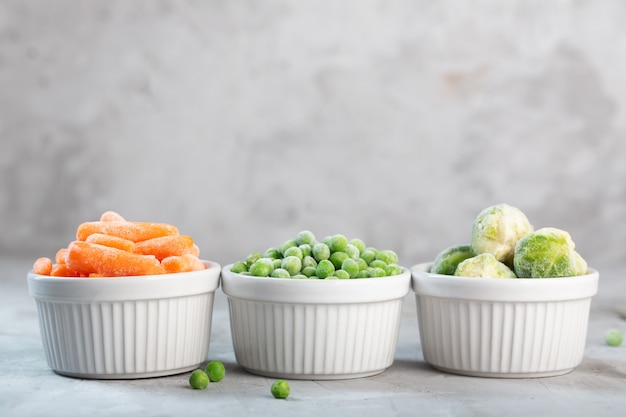 Frozen vegetables such as green peas, brussels sprouts and baby carrot in the white bowls on the concrete gray space