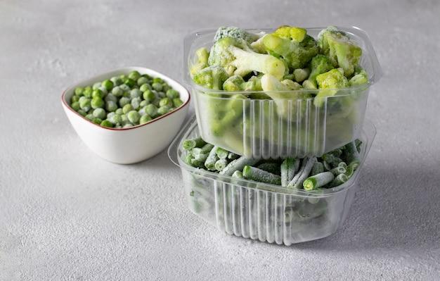 薄灰色の背景の収納ボックスにグリーンピース、インゲン、ブロッコリーなどの冷凍野菜。テキスト用のスペース