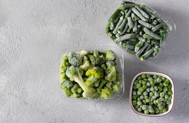 薄灰色の背景の収納ボックスにグリーンピース、インゲン、ブロッコリーなどの冷凍野菜。上から見た、コピースペース