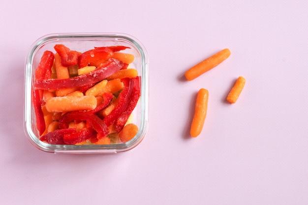 Замороженные овощи, такие как красный сладкий перец и морковь, в прозрачных мисках.