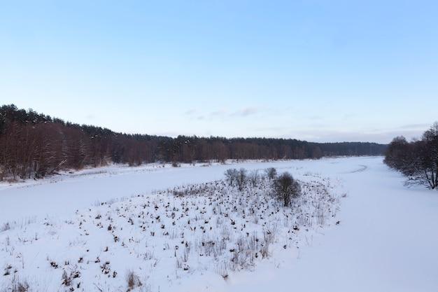 Замерзшая вода в реке в холодную погоду, зимний сезон с морозами и снегом