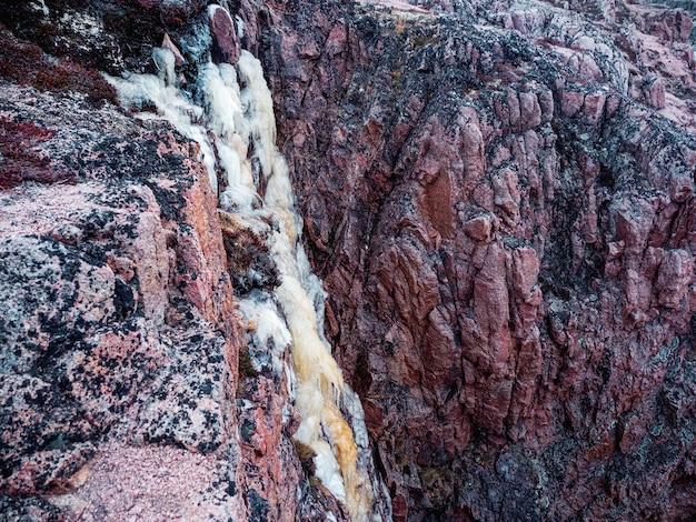 崖からの凍った滝。ロッキー山脈の頂上に氷河がぶら下がっている、大気のミニマリストの北極の風景。コラ半島。