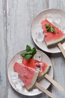 Frozen watermelon popsicles homemade ice cream with mint on white plate.
