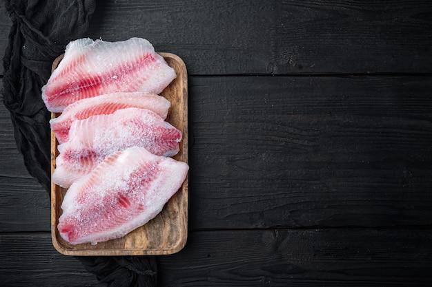 Замороженное филе белой рыбы, на черном деревянном столе, вид сверху