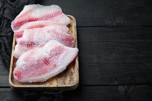 Замороженное филе белой рыбы на черном деревянном столе