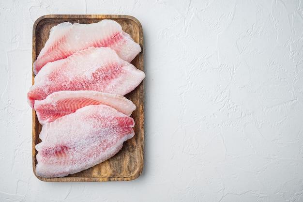 Замороженное филе белой рыбы, на белом столе, вид сверху