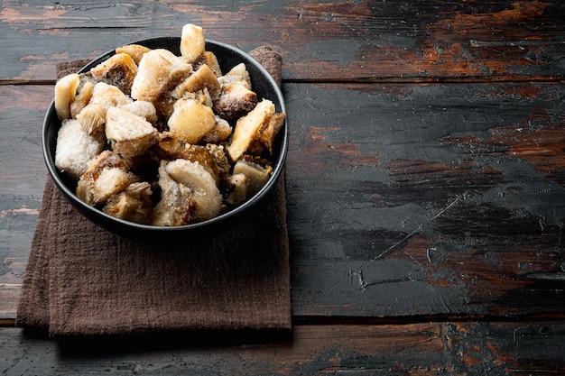 냉동 야생 버섯 세트, 그릇, 오래된 어두운 나무 테이블 배경, 텍스트 복사 공간