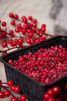 테이블에 그릇에 얼음으로 냉동 겨울 열매는 가지와 음식 흐리게 표면을 나뭇잎