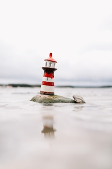 Замерзшее зимнее море с декоративным маяком. морской образ жизни. зима, море, путешествия, приключения, праздники и концепция отпуска. путешествие в 2021 году