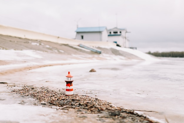 Замерзшее зимнее море с декоративным маяком. зима, море, концепция путешествия.