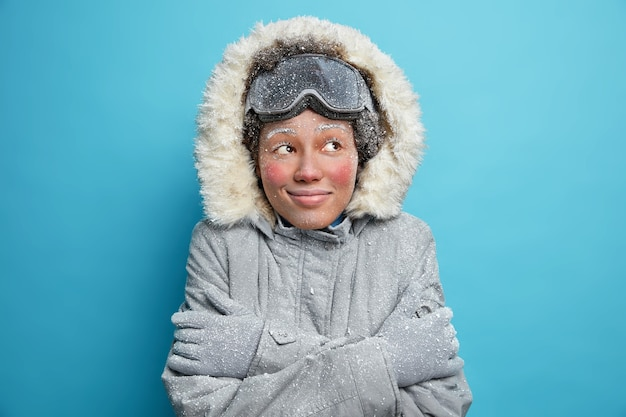 Frozen woman embraces herself trembles from cold covered with hoarfrost looks gladfully wears snowboard goggles winter jacket and gloves smiles pleasantly.