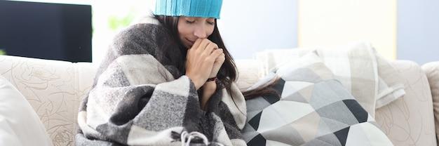 모자와 담요에 얼어붙은 여자는 소파에 앉아