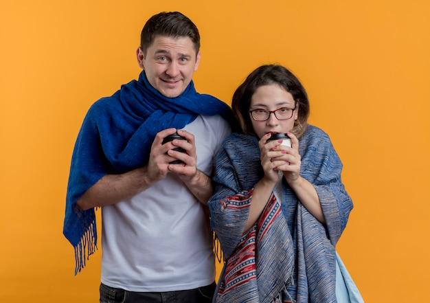 Giovani coppie congelate uomo e donna con coperte che tengono tazze di caffè in piedi sopra la parete arancione