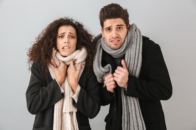 Замороженная молодая пара в свитерах и шарфах стоит изолированно над серой стеной и дрожит