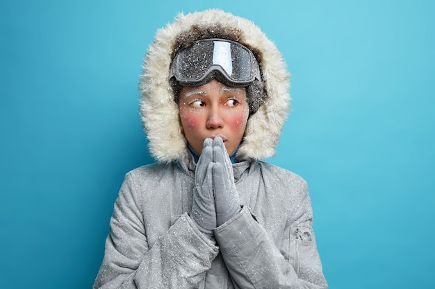 Frozen young ethnic woman tries to warm after spending long time at cold day keeps hands pressed together blows warm air wears grey jacket with hood has cold face covered with white hoarfrost