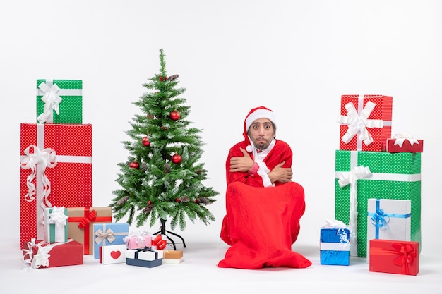 Frozen young man dressed as santa claus with gifts and decorated christmas tree sitting on the ground on white background