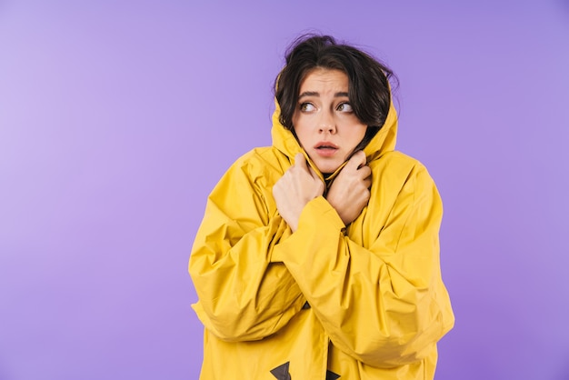 Frozen young woman in yellow raincoat posing isolated over purple wall wall looking aside.