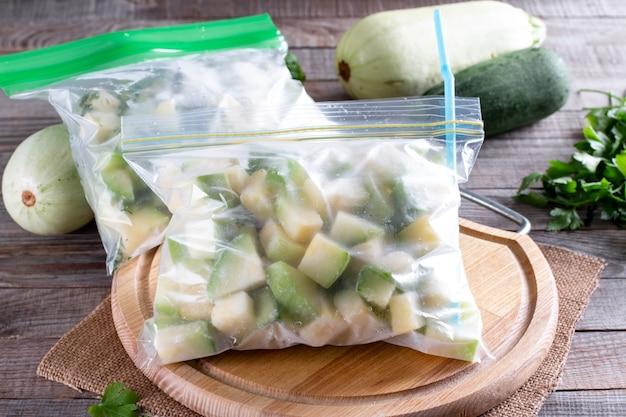 木製のテーブルの上のビニール袋で冷凍ズッキーニ。冷凍食品のコンセプト