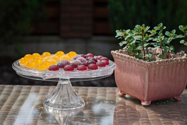 フルーツとベリーのマーマレードのお菓子、透明なガラスのペストリーにゼリーのお菓子、鍋にミント。