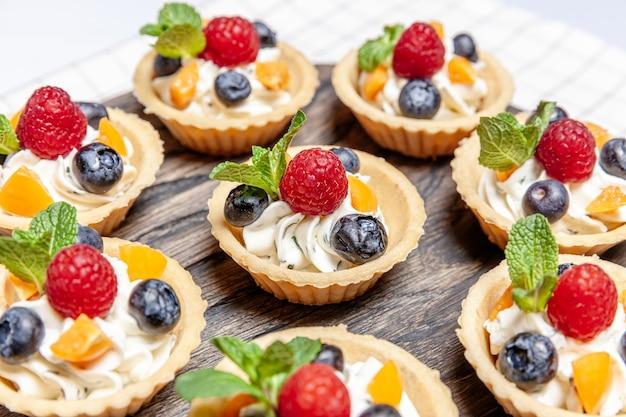木製トレイに盛り合わせたフルーツとベリーのタルトデザート。おいしいペストリースイーツのクローズアップは、新鮮な天然ラズベリーブルーベリーとチーズクリームでカラフルなケーキをパイします。フランスのパン屋のケータリング。