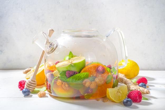 ティーポットのフルーツとベリーティー。レモン、ミント、ブルーベリー、生姜、オレンジ、リンゴの温かい飲み物。白い木製の背景のコピースペースにホットフレーバースチーム飲料