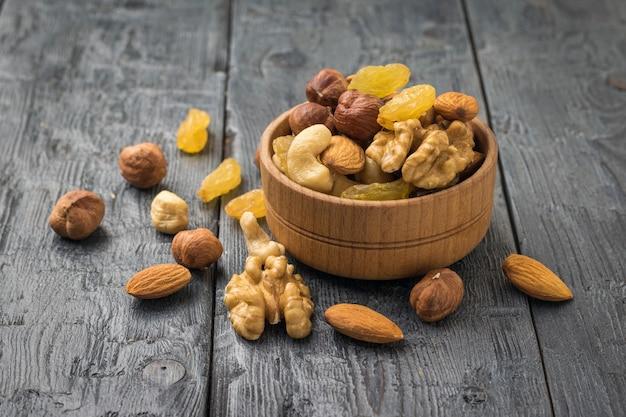Смесь фруктов и орехов в деревянной миске на деревянном столе. натуральная здоровая вегетарианская пища.
