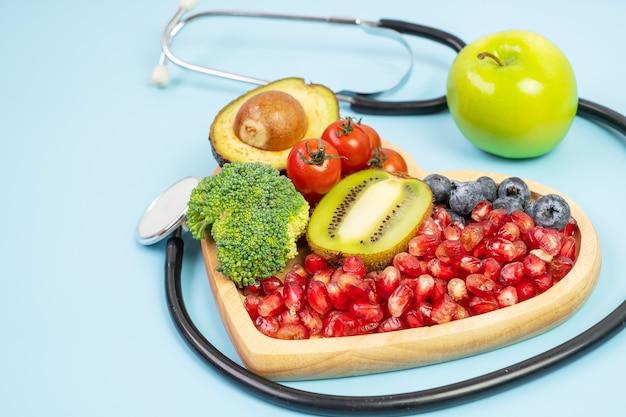 Фрукты и овощи; черника, помидоры черри, авокадо, брокколи, киви и зеленое яблоко на синем фоне. потеря веса, питание, здоровое питание, диета и вегетарианская концепция