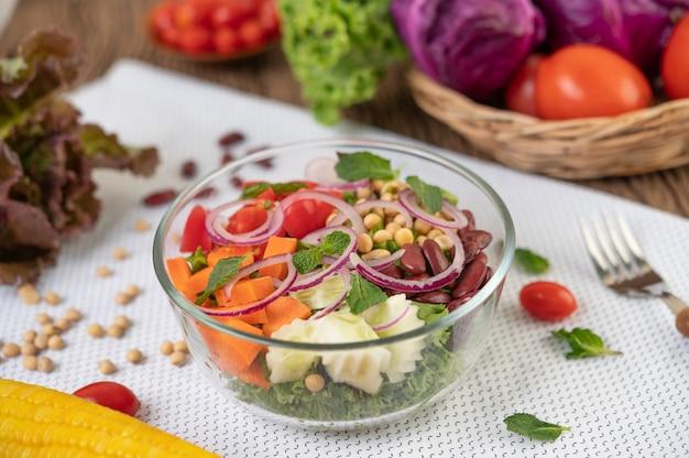 白い地面にガラスのカップで果物と野菜のサラダ