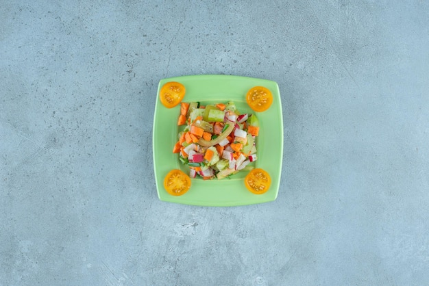 青に具材を混ぜた果物と野菜のサラダ。