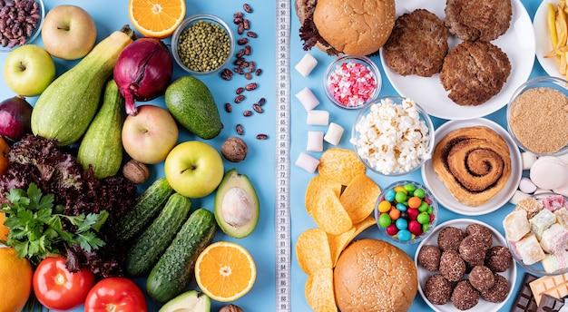 Фрукты и овощи против сладостей и фаст-фуда, вид сверху, лежал на синем фоне