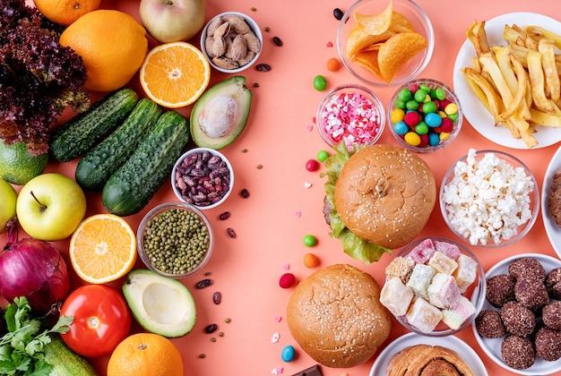 Фрукты и овощи против сладостей и фаст-фуда, вид сверху, лежал на оранжевом фоне