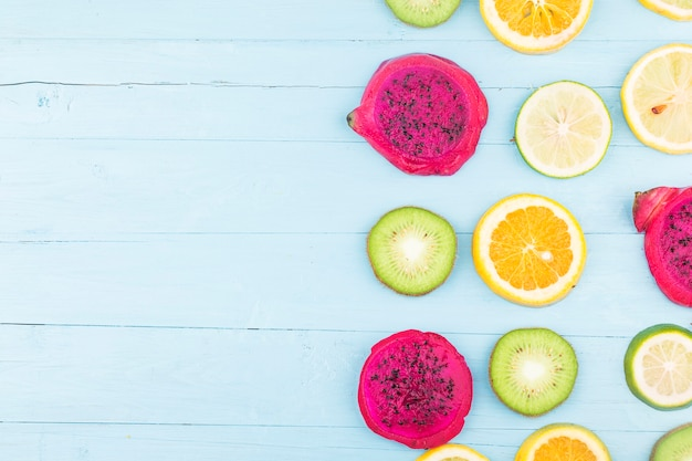 フルーツの背景。青い木の板にカラフルな新鮮な果物。オレンジ、ドラゴンフルーツ、レモン、フラット横たわっていた、トップビュー、