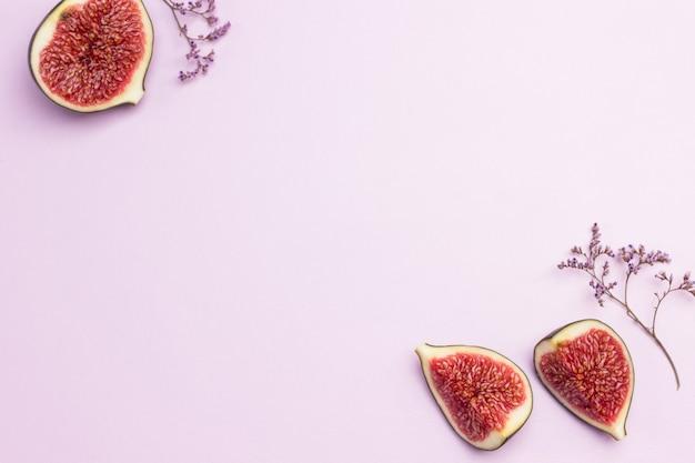 果物の背景。背景の側面にイチジクの半分。ピンクの背景。フラットレイ。コピースペース