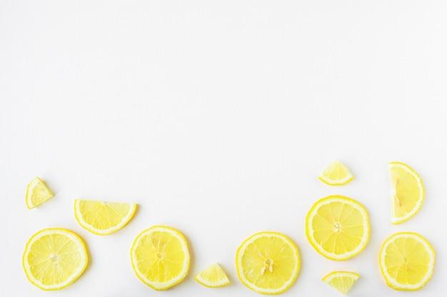 Фруктовый фон с ломтиками лимона вид сверху нарезанные желтые фрукты на белом деревянном столе