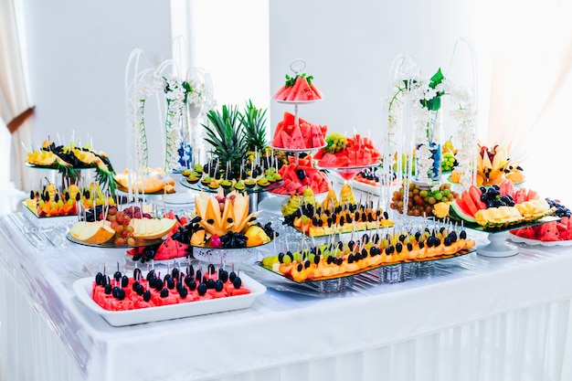Fruit bar at wedding reception. restaurant hall. luxury catering