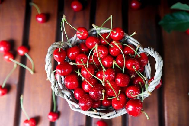 木製のテーブルトップビューのフルーツバスケット。ベリーを収穫します。熟したサクランボと夏の背景。