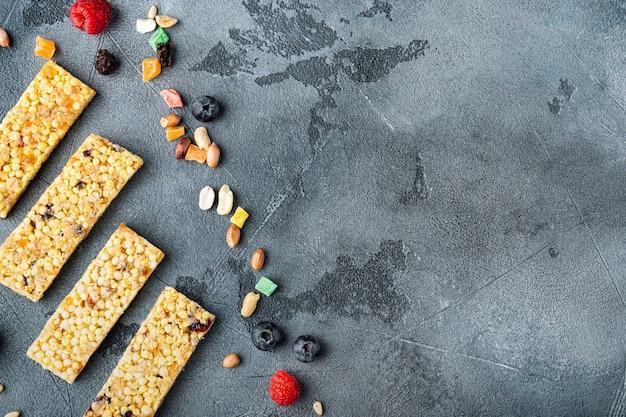 과일 베리와 너트 에너지 바. 회색 배경에 건강한 간식, 복사 공간이 있는 위쪽 전망