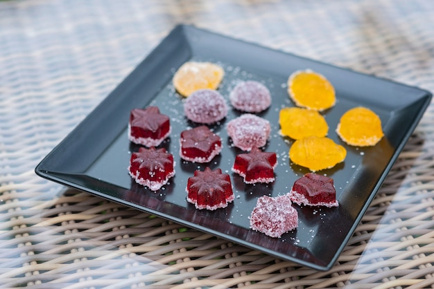 Fruit and berry marmalade sweets, jelly sweets on a black plate.