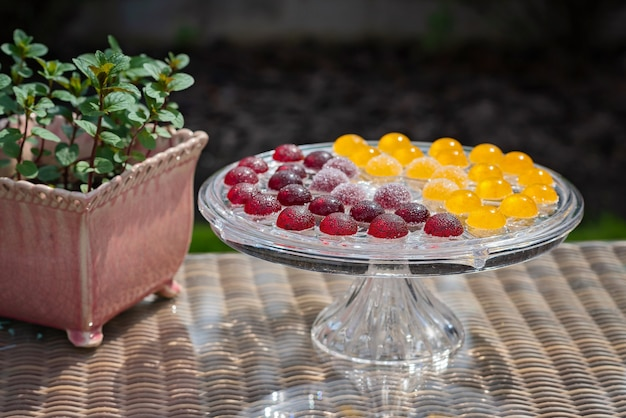 Fruit and berry marmalade sweets, jelly sweets on a transparent glass pastry stand with mint in a pot.