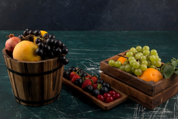 Fruit and berry mix in wooden containers on blue space