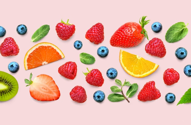 Fruit and berry pattern of various ripe berries and leaves on pink background
