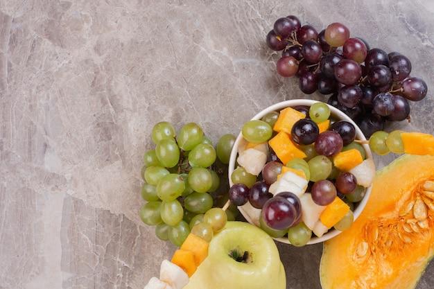 Ваза с фруктами и свежие фрукты на мраморной поверхности.