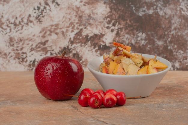 Ваза с фруктами, вишневые яблоки и свежее яблоко на мраморном столе.