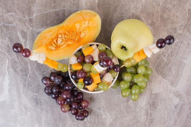 Coppa di frutta e frutta fresca sulla superficie in marmo.