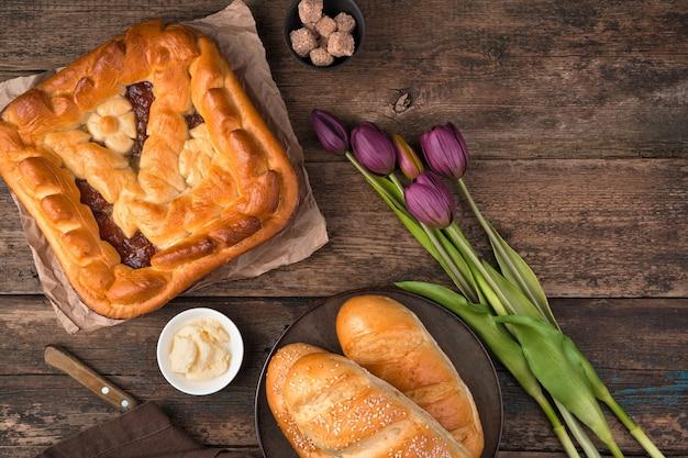 Фруктовый торт, булочки и букет тюльпанов на деревянном фоне. вид сверху с пространством для копирования.
