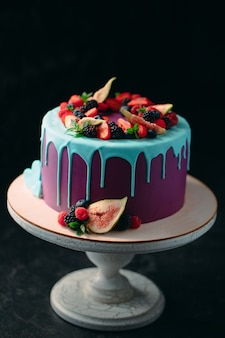 Fruit cake decorated with figs, blueberries, raspberries and mint.