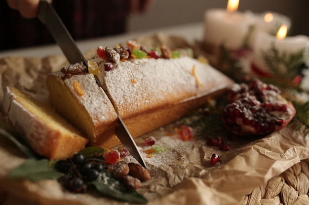 Fruit cake dusted sliced with icing, nuts, kernels pomegranate and dry orange close-up. christmas and winter holidays homemade cake