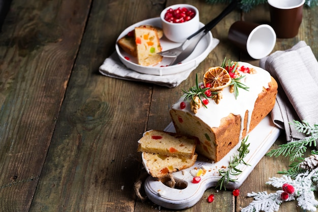 Fruit cake dusted sliced with icing, nuts, kernels pomegranate and dry orange old wooden . christmas and winter holidays homemade cake