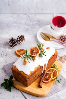 Fruit cake dusted with icing, nuts and dry orange on stone . christmas and winter holidays homemade cake