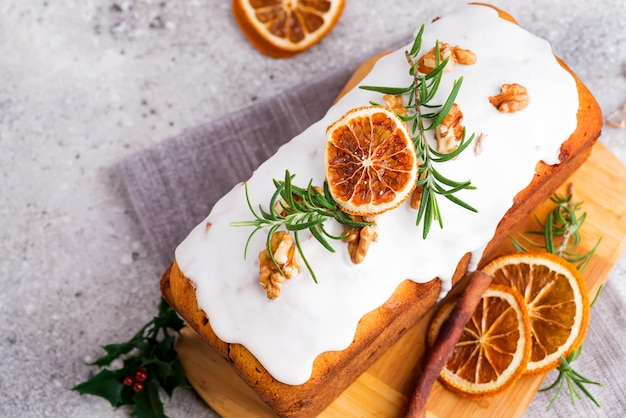 Fruit cake dusted with icing, nuts and dry orange stone , flat lay. christmas and winter holidays homemade cake